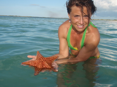 Jane checks out the bright orange colours on a Bahama sea star or starfish