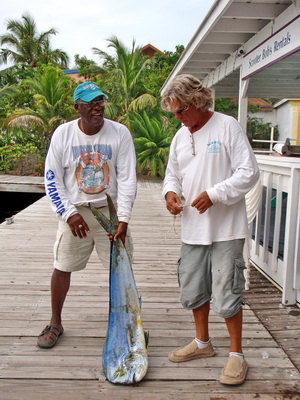Ossie and Scooter check the weight on a dorado caught by Chucke 11.
