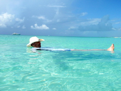 Sheldon floats on a turquoise blue ocean wishing the private yacht anchored out was his.