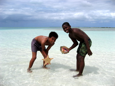 The boys were having fun finding starfish and a conch while their Dad or uncle continued sitting and fishing.