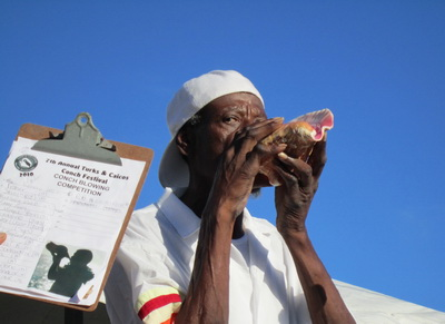A competitor in the conch blowing contest dressed in traditional Turks and Caicos Island national costume.