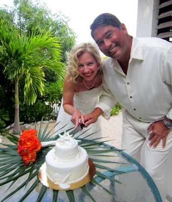 "A little back to front as Lori and Dan ""cut"" their wedding cake out side their villa at Harbour Club."