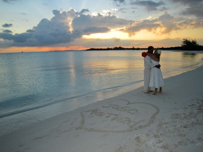 """Just Married"" written in the sand surrounded by a giant heart. Lori's beautiful ring and bridal bouquet of large orange roses with a touch of calm seas and horizon in the background."